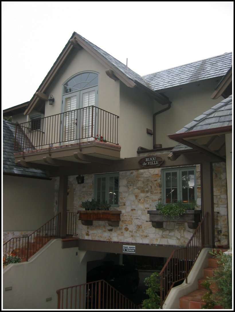 Street view of custom stone detailing, iron balcony railings, wood corbels, planters